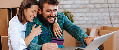 Couple hugging while looking at computer screen with credit card in hand